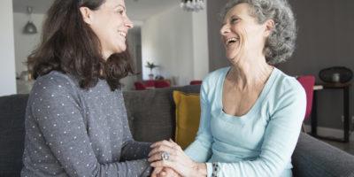 Junge Frau besucht ältere lachende Frau